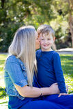 Mother kissing young son on cheek whilst sitting together outdoo Stock Images