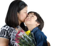 Mother kissong her son with flower Royalty Free Stock Image