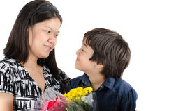 Mother kissong her son with flower Stock Photos