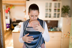 Mother in kitchen with her son in sling, kissing him. Beautiful young mother in kitchen with her baby son sleeping in sling at home, kissing him on head Royalty Free Stock Image