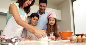 Mother kneading out dough with her family stock video footage