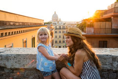 Mother kneeling by daughter above Rome at sunset Royalty Free Stock Images
