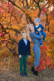 Mother lady womanwithTwo handsome cute brothers sitting on pumpkin in autumn forest alone stock photography