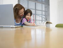 Mother With Laptop Assisting Daughter In Coloring Book At Table Royalty Free Stock Photo