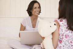 Mother With Laptop Looking At Daughter In Bed Royalty Free Stock Photos