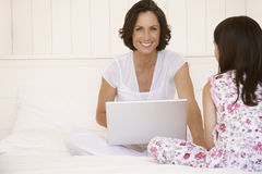 Mother With Laptop Sitting Next To Daughter Royalty Free Stock Photo