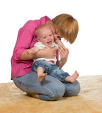 Mother with laughing baby. Mother kneeling on the floor with her laughing adorable baby cradled on her knees enjoyinga moment of joyful intimacy Stock Photos