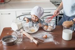 Mother and laughing happy child preparing dough. At kitchen royalty free stock images