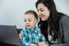 Mother laughing while holding her boy. Mother with her toddler son looking at the computer's screen and laughing Royalty Free Stock Image
