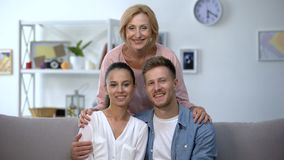 Mother-in-law hugging young couple showing hands with engagement rings at home. Stock footage stock video footage