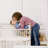 Mother laying son down into crib