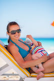 Mother laying on sunbed and holding baby. Drinking water Stock Photo