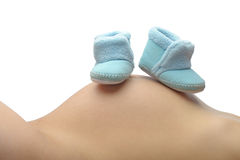 Mother lays back and rests her unborn childs shoes Stock Photography