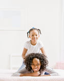 Mother lays on bed with playful daughter royalty free stock photo