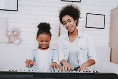 Mother Learn Little Girl Play on Piano. Happy Girl royalty free stock photos