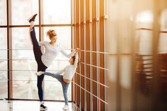 Mother learning daughter to make a high leg strech Stock Image
