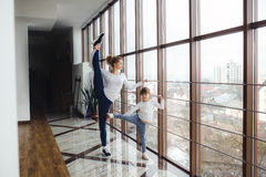 Mother learning daughter to make a high leg strech Royalty Free Stock Photo