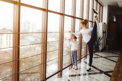 Mother learning daughter to make a high leg strech Stock Photos