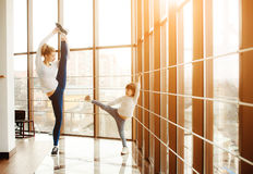 Mother learning daughter to make a high leg strech Stock Photography