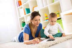 Mother learning her child how to drawing. With wax colors royalty free stock images