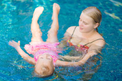 Mother learns daughter to relax in pool water at tropical beach Royalty Free Stock Photos
