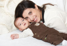 Mother lie with baby on bed, happy family portrait on white background Royalty Free Stock Photos