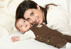 Mother lie with baby on bed, happy family portrait on white background, yellow toned Stock Photos