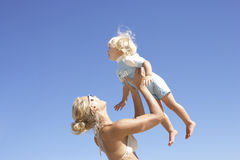 Mother lifting daughter (2-4) above head, smiling, profile Royalty Free Stock Photography