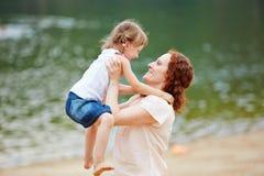 Mother lifting daughter Stock Photo