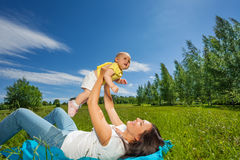 Mother lifting her baby up with straight arms Stock Photo