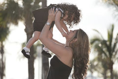 Mother lifting her daughter Stock Image