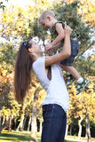 Mother lifting her son at park. Young boy laughing on mother's arms at park royalty free stock photos