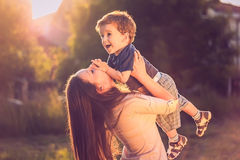 Mother lifting son. In the air with sun in the background Royalty Free Stock Photos