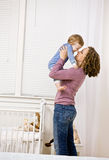 Mother lifting son from crib in bedroom Royalty Free Stock Photography