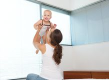 Mother lifting up and playing with a happy baby Royalty Free Stock Photo