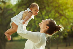 Mother Lifting Up And Turning Around Little Baby Daughter In Par Stock Photography