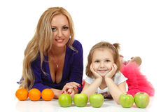 Mother with liitle daughter with apples and oranges Stock Photography