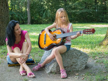 Mother listening daughter playing guitar. Mother teaching and listening daughter playing guitar Royalty Free Stock Photography