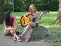 Mother listening daughter playing guitar. Mother teaching and listening daughter playing guitar Stock Photos