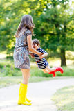 Mother and little adorable child girl in rubber boots having fun Stock Photo