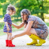 Mother and little adorable child girl in rubber boots having fun Stock Photography