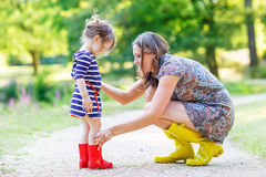 Mother and little adorable child girl in rubber boots having fun. Young mother and little adorable child girl in rubber boots having fun together, family look Royalty Free Stock Photography