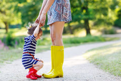 Mother and little adorable child girl in rubber boots having fun Stock Photos