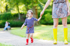 Mother and little adorable child girl in rubber boots having fun Stock Images
