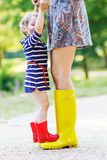 Mother and little adorable child girl in rubber boots having fun royalty free stock image