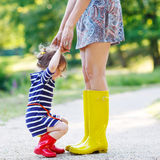 Mother and little adorable child girl in rubber boots having fun Stock Image