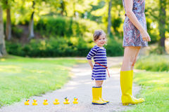 Mother and little adorable child in yellow rubber boots Royalty Free Stock Image