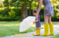 Mother and little adorable daughter in yellow rubber boots, fami Royalty Free Stock Images