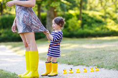 Mother and little adorable daughter in yellow rubber boots, fami Stock Photo