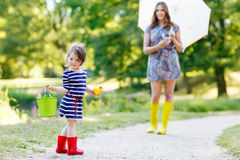 Mother and little adorable kid girl daughter in rain boots Royalty Free Stock Photography